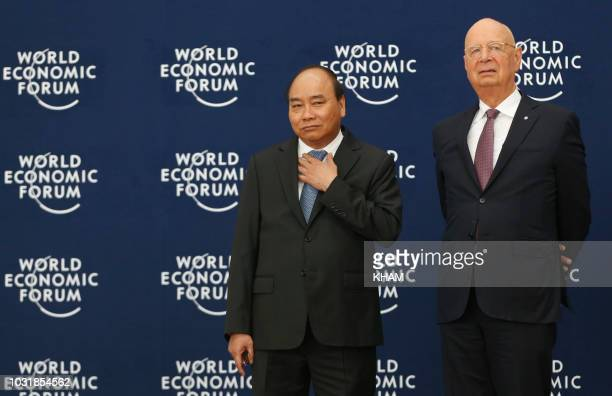 Vietnam's Prime Minister Nguyen Xuan Phuc and World Economic Forum's founder and executive chairman Klaus Schwab wait to greet guests during the...