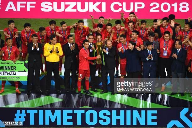 Vietnam's Prime Minister Nguyen Xuan Phuc awards the AFF Suzuki Cup 2018 championship trophy to Vietnam's forward Nguyen Van Quyet after Vietnam won...