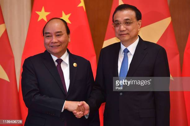 Vietnam's Prime Minister Nguyen Xuan Phuc, left, shakes hands with Chinese Premier Li Keqiang as they pose for media before their meeting on April...