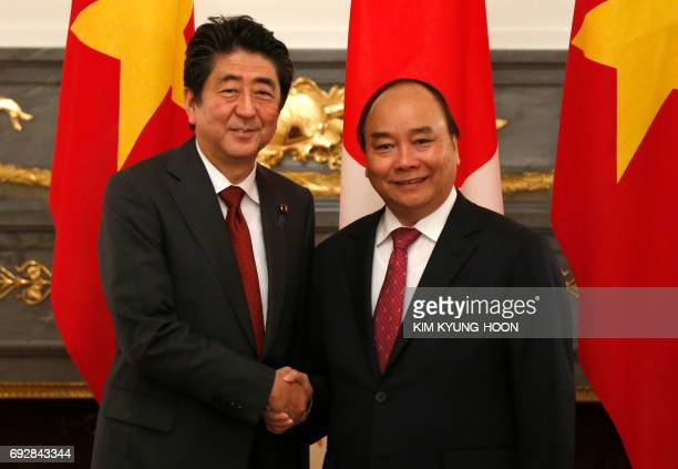 Vietnam's Prime Minister Nguyen Xuan Phuc shakes hands with Japan's Prime Minister Prime Minister Shinzo Abe in Tokyo on June 6 2017 Phuc is in Japan...