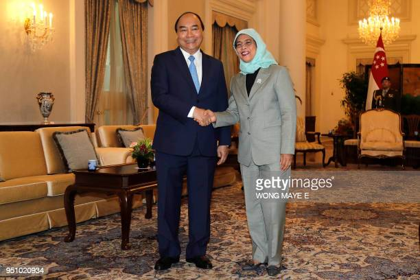 Vietnam's Prime Minister Nguyen Xuan Phuc shakes hands with Singapore's President Halimah Yacob  at the start of their meeting at the Istana...