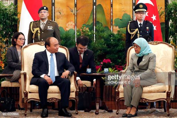 Vietnam's Prime Minister Nguyen Xuan Phuc talks to Singapore's President Halimah Yacob  during their meeting at the Istana presidential palace in...