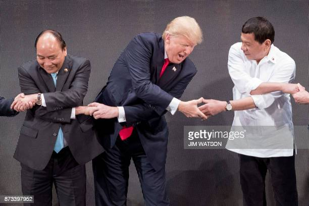 TOPSHOT Vietnam's Prime Minister Nguyen Xuan Phuc US President Donald Trump and Philippine President Rodrigo Duterte join hands for the family photo...