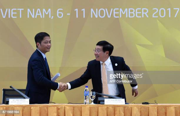 Vietnam's Trade Minister Tran Tuan Anh and Vietnam's Foreign Minister Phm Bình Minh shake hands at the end of the AMM press conference during the...