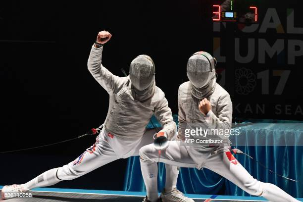 Vietnam's Vu Thanh An and Thailand's Voragon Srinualnad react during their men's sabre individual fencing final of the 29th Southeast Asian Games in...
