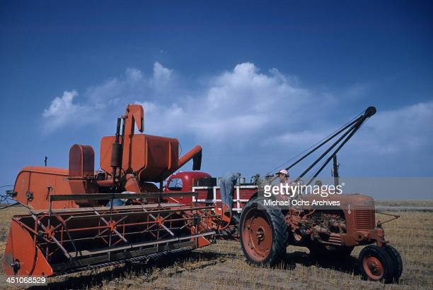 A view a combine harvester tractor and a pickup truck in a wheat field during harvest in Oakley Kansas