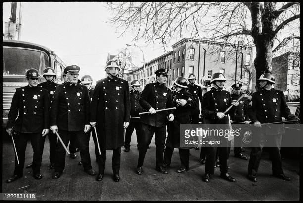View a line of police officers with batons and riot gear across an unspecified Brooklyn street, New York, New York, July 16, 1964. Following a police...