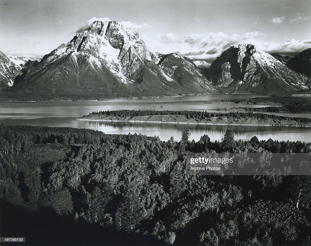 View across a river valley towards Mount Moran in the Teton Range in Grand Teton National Park, Wyoming, 1941.
