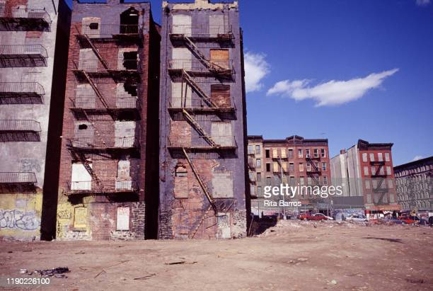 View across a vacant lot surrounded by abandoned and boarded up buildings Harlem New York New York 1997