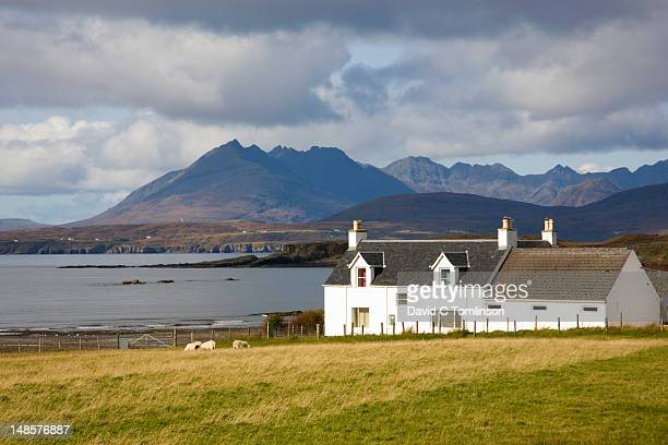 View across field near Tarskavaig to Cuillin hills, whitewashed house in foreground, Sleat Peninsula.