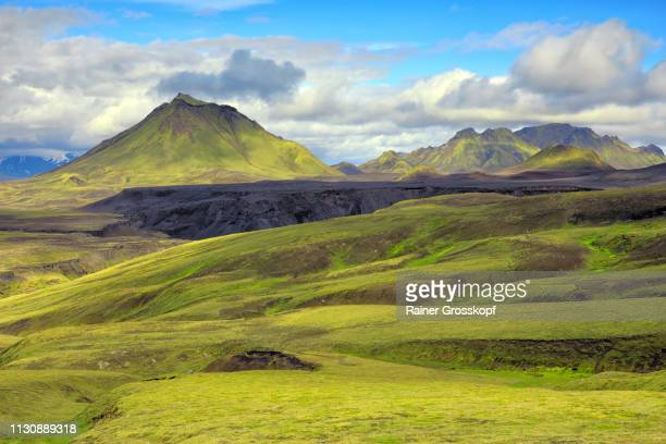 View across grassy and mossy green open land to mountain Hattafell