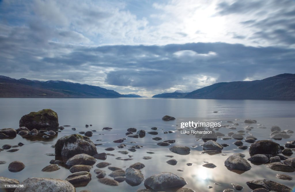 A view across Loch Ness looking down the length of the lake with rocks inn the foreground and dark clouds above, in Scotland : Stock Photo
