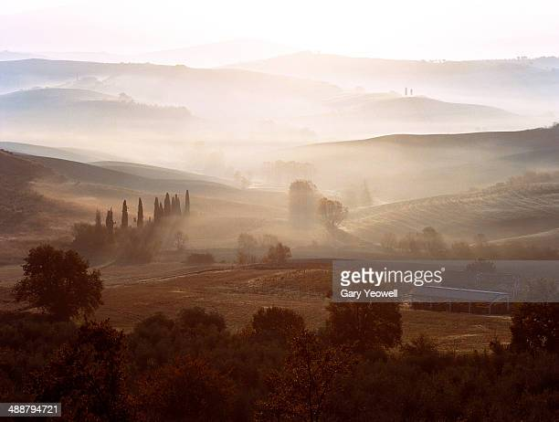 view across misty tuscan landscape at dawn - yeowell stock pictures, royalty-free photos & images