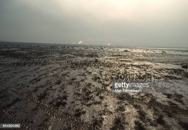 View across oilsoaked sand as oil wells burn in the distance Kuwait 1991