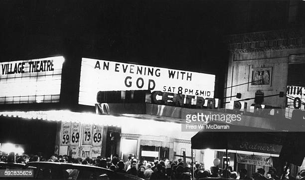 View across Second Avenue of a crowd of people under the marquee for the Fillmore East which advertises 'An Evening with God' New York New York May...