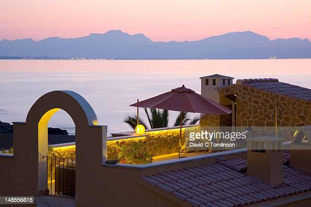 View across the Badia dÆAlcudia after sunset, Betlem, near Colonia de Sant Pere, with illuminated roof terrace in foreground.