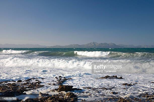 View across the Badia dÆAlcudia towards Cap des Pinar, with crashing surf in foreground.