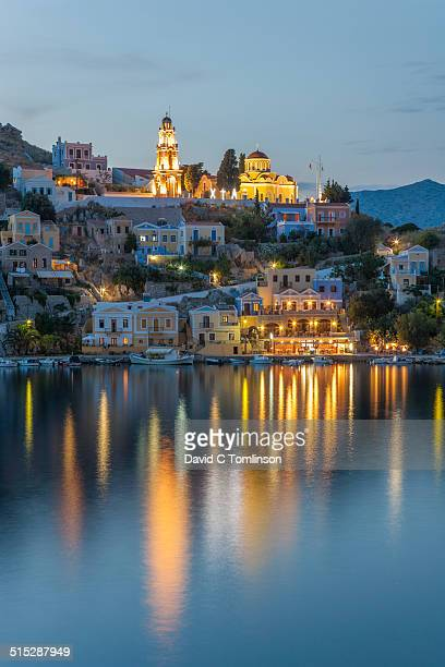 view across the harbour at dusk, gialos, symi - symi foto e immagini stock