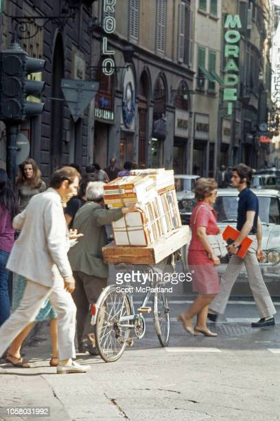 View across the intersection of busy streets Florence Italy August 1968 Among the visible pedestrians one man walks a bicycle stacked with boxes of...