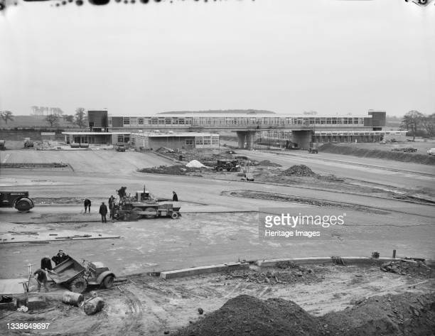 View across the Keele Service Area during the construction of the Birmingham to Preston Motorway , showing a team of workers in the foreground laying...