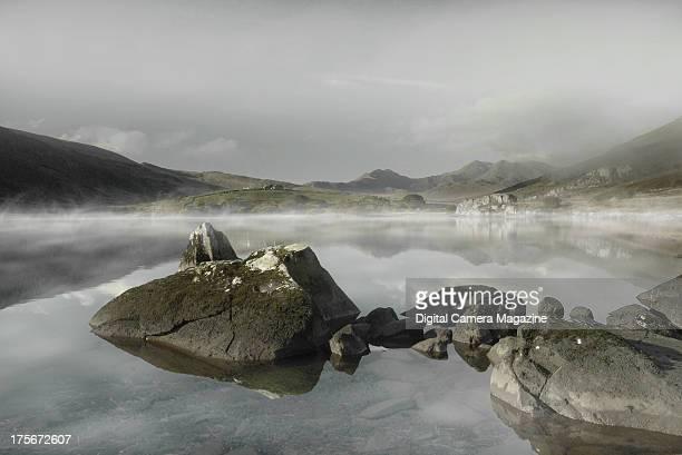 View across the misty Llynnau Mymbyr lakes near the village of Capel Curig in the Dyffryn Mymbyr valley of Snowdonia Wales on December 19 2012