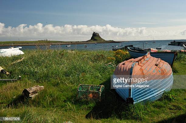 View across the Northumberland coastline to Bamburgh Castle with small fishing boats and lobster cages in the foreground