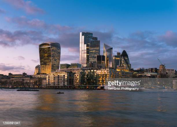 view across the river thames of the city of london's illuminated financial district skyline at dusk - tim grist stock pictures, royalty-free photos & images