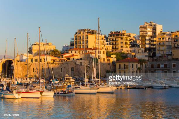 view across the venetian harbour at sunset, iraklio, crete, greece - herakleion stock photos and pictures