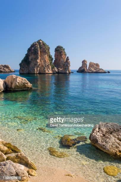 view across tranquil cove to the faraglioni, a series of towering offshore rock stacks, scopello, trapani, sicily, italy, mediterranean, europe - isola di capri foto e immagini stock