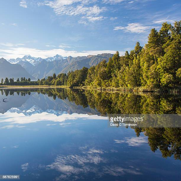 view across tranquil lake matheson, fox glacier - international landmark stock pictures, royalty-free photos & images