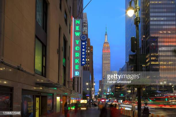 """view along 34th street at illuminated empire state building at dusk with a """"new yorker"""" neon sign - rainer grosskopf stock-fotos und bilder"""