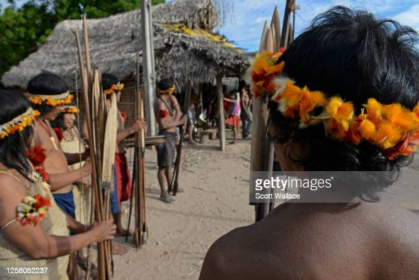 View along a line of Awa men and women, many adorned with toucan and macaw feathers & holding hunting bows and arrows, in their village in the Caru...