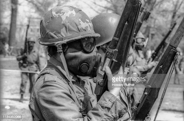View along a line of Ohio National Guardsmen with rifles and gas masks on the Kent State University campus as they prepare to disperse student...