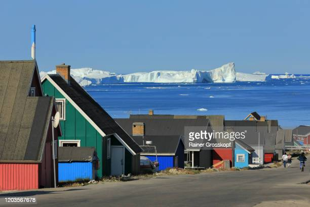 view along a road between colorful wooden houses with icebergs in the background - rainer grosskopf fotografías e imágenes de stock