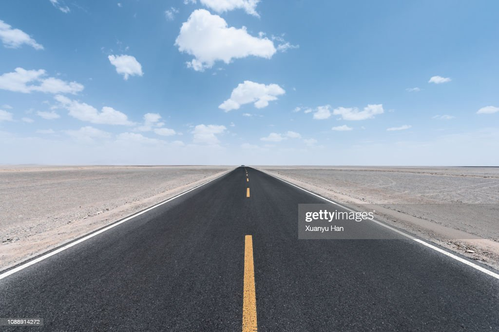 View along a straight asphalted road through desert : Stock Photo