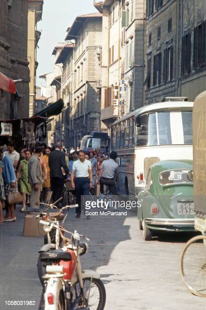 View along a street crowded with pedestrian and vehicle traffic Florence Italy August 1968