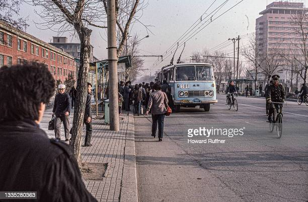 View, along an unidentified street, as passengers board an articulated electric bus at a stop, Shenyang, Liaoning, China, April 1986.