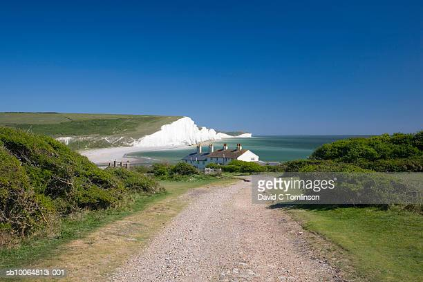 View along coastal path towards houses and the Seven Sisters cliffs, Seaford Head, Sussex, England, UK