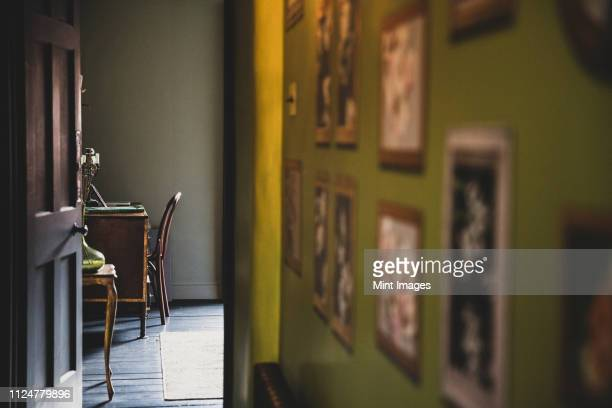 view along corridor with vintage pictures on green wall, open brown wooden door to study with antique desk and chair. - the past stock pictures, royalty-free photos & images