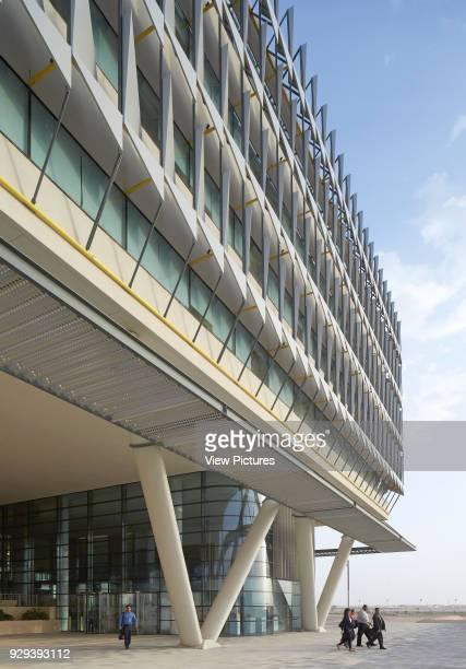 View along exterior facade with canopied main entrance. Siemens Masdar, Abu Dhabi, United Arab Emirates. Architect: Sheppard Robson, 2014.