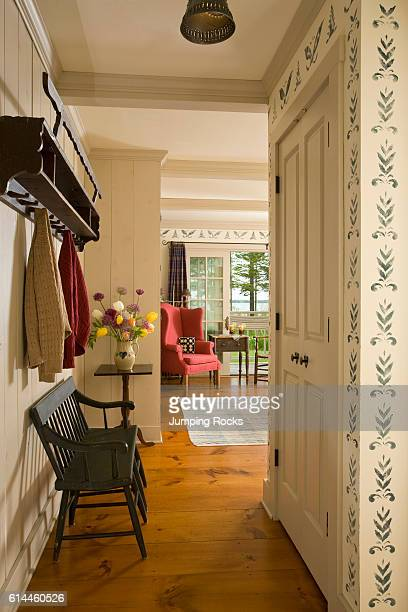 View along hallway with wooden bench seat facing built in cupboard in country style