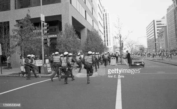 View along K Street NW as police officers, with their batons out, run toward fleeing anti-KKK demonstrators during a protest, Washington DC, November...