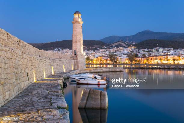 View along sea wall of the Venetian Harbour to historic lighthouse, dusk, Rethymno, Crete, Greece