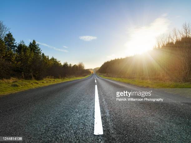 view along straight country road in ulster, northern ireland at sunset. - road stock pictures, royalty-free photos & images