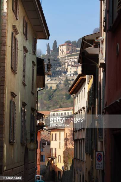view along street in citta alta of bergamo to western outskirts - bergamo alta foto e immagini stock