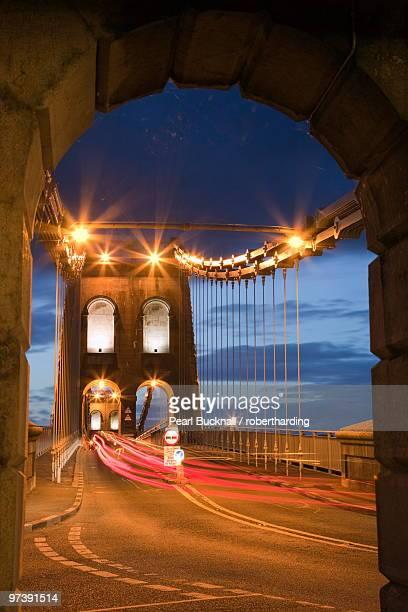 view along the a5 road at night across the menai suspension bridge, built by thomas telford in 1825, bangor, gwynedd, north wales, united kingdom, europe. - ponte sospeso di menai foto e immagini stock