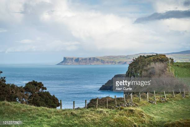 view along the north antrim coast, northern ireland with distant cliffs - county antrim stock pictures, royalty-free photos & images