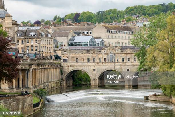 view along the river avon towards famous pulteney bridge, bath, uk - bath england stock pictures, royalty-free photos & images