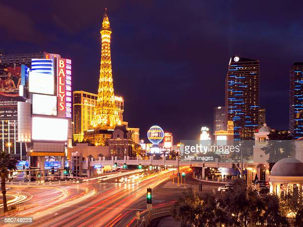 View along the Strip in Las Vegas at night, with the illuminated Paris Las Vegas Hotel and Casino in the background.