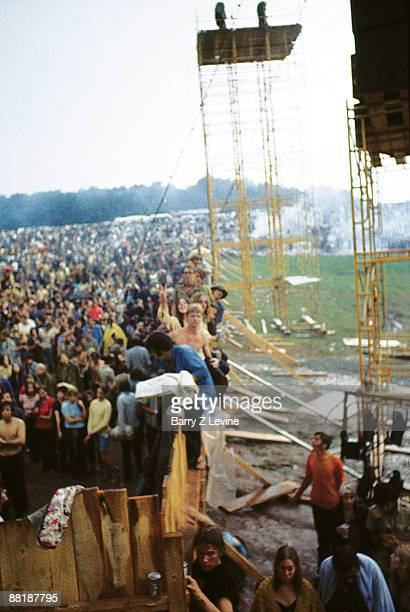View along the wooden fence at the edge of the Woodstock Music and Arts Fair as in the distance rain extinguishes several fires in clouds of smoke...